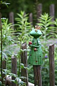 Ceramic frog prince on top of rustic paling fence