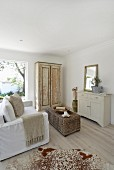 Living room in sandy shades with old cupboard and wicker trunk