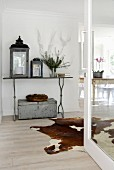 Lanterns on metal table and cow-hide rug in foyer