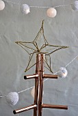 Golden wire star on Christmas tree made from copper piping