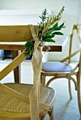 Green branches tied to chair back with strip of hessian
