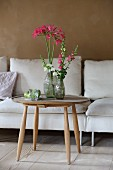 Vases of agapanthus and snapdragons on round wooden table in living room