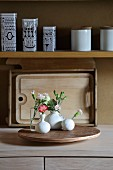 Small vases of flowers on lazy Susan covered in patterned wood veneer in kitchen