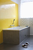 Grey-clad bathtub against bright yellow wall