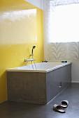 Grey-clad bathtub against bright yellow wall