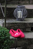 Pink, hand-made felt slippers and candle lantern on vintage stone steps