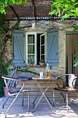 Vintage Metallstühle und Klapptisch auf rustikaler Terrasse