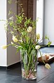 Glass vase of tulips on floor