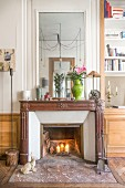 Lit candles in fireplace with large mirror above old mantelpiece