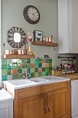 Wooden shelves and mirror with tiled surround above kitchen sink