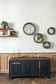 Round mirrors above modern sideboard against wainscoting