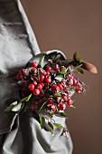 Bouquet of rose hips in vintage knapsack