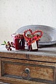 Jars of jam decorated with rose-hip love-heart on top of vintage chest of drawers