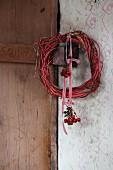 Weidenkranz mit Hagebuttensträußchen an rot-weißem Schleifenband aufgehängt vor Vintage Wand mit Holztür