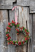 Romantic heart-shaped wreath of rose hips and moss hung on rustic board wall