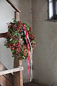 Autumn wreath of rose hips, moss and red and white ribbons on newel post of vintage wooden stairs