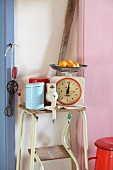 Vintage kitchen scales, manual coffee mill and tins on step-stool