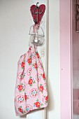 Fabric bag and tealight holder hung on white wooden batten with love-heart