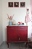 Vintage chest of drawers decorate with candles and branches of red berries