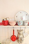 Romantic crockery on wall-mounted shelf with kitchen utensils hung from underside