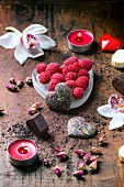 Chocolate candies heart shaped with dry tea roses, fresh raspberries and orchids for Valentine s Day
