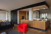 Moderner Kücheneinbau in offenen Wohnraum mit schwarzer Metallverkleidung, Eichenboden und rotem Polstersessel
