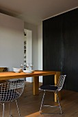 Solid oak table and metal chairs in front of black metal cladding