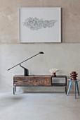 Schlichtes Lowboard aus wiederverwendetem Holz mit schwarzer Tischleuchte vor gerahmtem Kunstobjekt