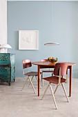 Essplatz mit Retro Tisch und Stühlen und moderner Pendelleuchte vor hellblauer Wand