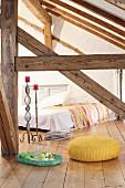 Gelber, gestrickter Sitzpouf im Dachzimmer eines Fachwerkhauses