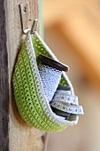 Green crocheted basket hung from hook on wooden board