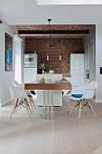 Moderner Esstisch in offener Küche mit Backsteinwand und Gewölbe