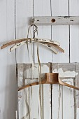 Old clothes hangers and tape measure hung from peg and from shutter