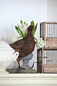 Arrangement of stuffed pheasant next to hyacinths and cages