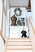 Hund liegt vor einer Kommode mit Vintagestücken an der Treppe