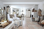 Terracotta-tiled floor and collection of vintage pieces in white interior