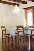 Dining table, rustic wooden chairs and white classic chairs below chandelier