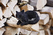 Hand-made, felted, woollen cat on log