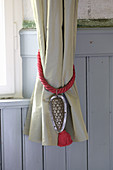 Curtain tie-back decorated with tassel and old cake tin