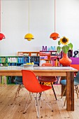 Shell chairs of various colours at long wooden table in front of colourful shelves