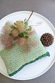 Green crocheted cushion made from T-shirt yarn on round coffee table