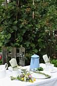 Gedeckter Gartentisch mit buntem Wiesenblumenstrauss und hellblauer Emaillekanne