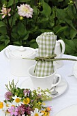 Green gingham linen napkin in white coffee cup