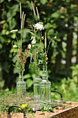 Wildflowers and blades of grass in vintage glass bottles on vintage wooden crate