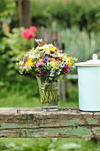 Vase of colourful wildflowers on vintage wooden beam in garden