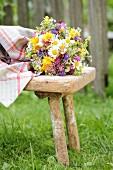 Bunter Wiesenblumenstrauss auf Vintage Holzschemel im Grünen