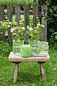 Stillleben mit Garn umwickelten Glasgefässen und bunten Wiesenblumen auf Vintage Holzschemel