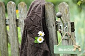Flowers pinned to cardigan hung from vintage garden gate next to sign
