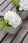 White hydrangeas and lady's mantle in buckets on wooden surface