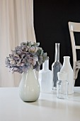 Collection of vases and pale blue hydrangea on white table